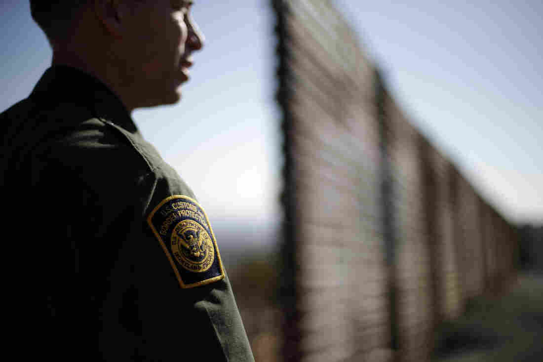 A Border Patrol agent looks to the north near where the border wall ends as is separates Tijuana, Mexico, left, and San Diego, right.