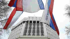 Flags fly outside the Crimean parliament building in Simferopol on Thursday during a rally by pro-Russian protesters. Gunmen seized government buildings in the city.