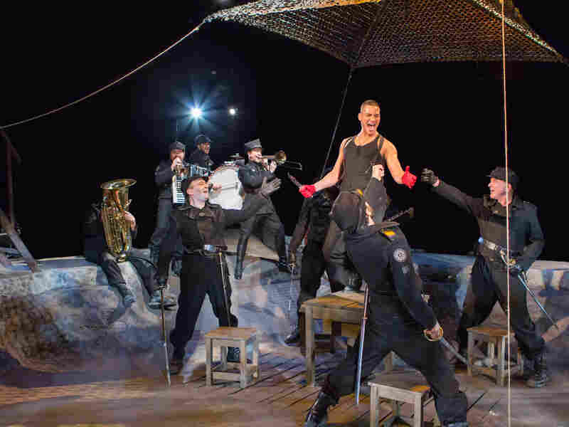 Arena Stage's in-the-round production also stars Nicholas Rodriguez (center) and an ensemble of instrument-playing actors who provide rowdy accompaniment for the show's songs.