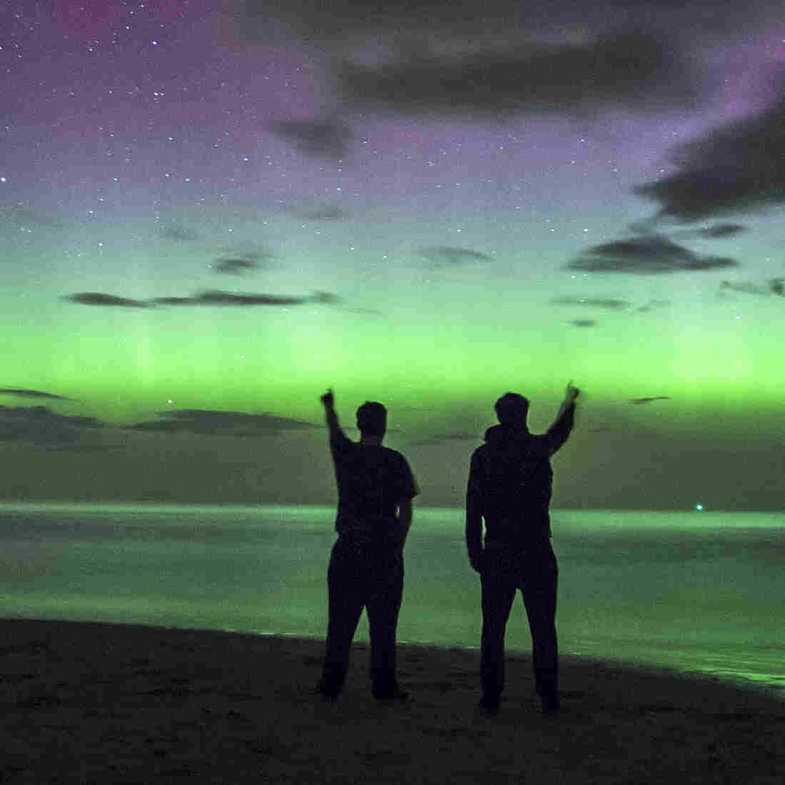 People view the Northern Lights over Bamburgh Castle Beach Thursday in Northumberland, England. A powerful solar flare caused the aurora borealis to be  visible farther south than usual.