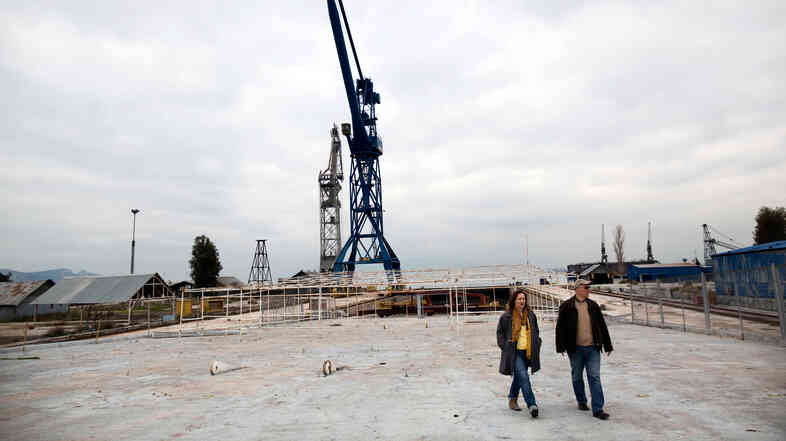 Alexandra Tsitoura (left) and Nikos Aivatzidis walk through now-empty Hellenic Shipyards in Athens, Greece. Two years ago, the shipyard employed around 1,100 workers.