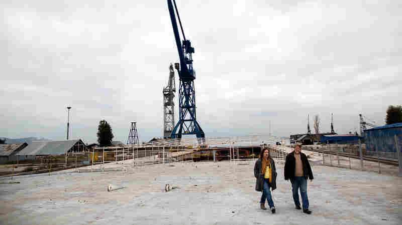 Alexandra Tsitoura (left) and Nikos Aivatzidis walk through now-empty Hellenic Shipyards in Athens, Greece. Two years ago, the shipyard employed around 1,100 workers.