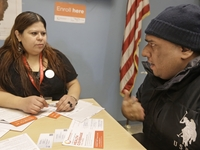 Yuvania Maldonado, a counselor for President Obama's health care law, speaks with Chicago taxi driver Mohammad Chaudri at a city office where taxi drivers go to renew their license.