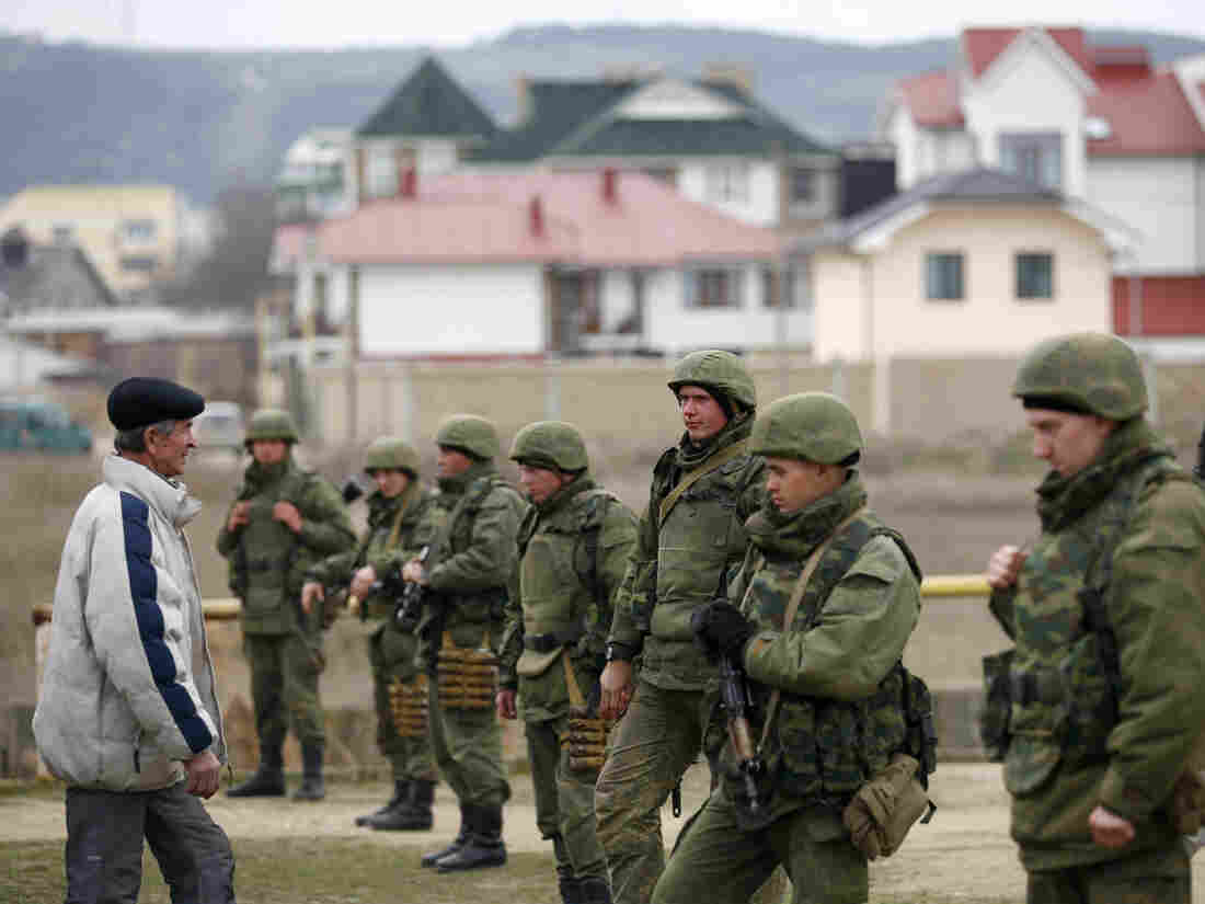 Ukrainian military personnel stand guard in the Crimean port city of Feodosia on Sunday. Ukraine is mobilizing for war, calling up reserve troops.