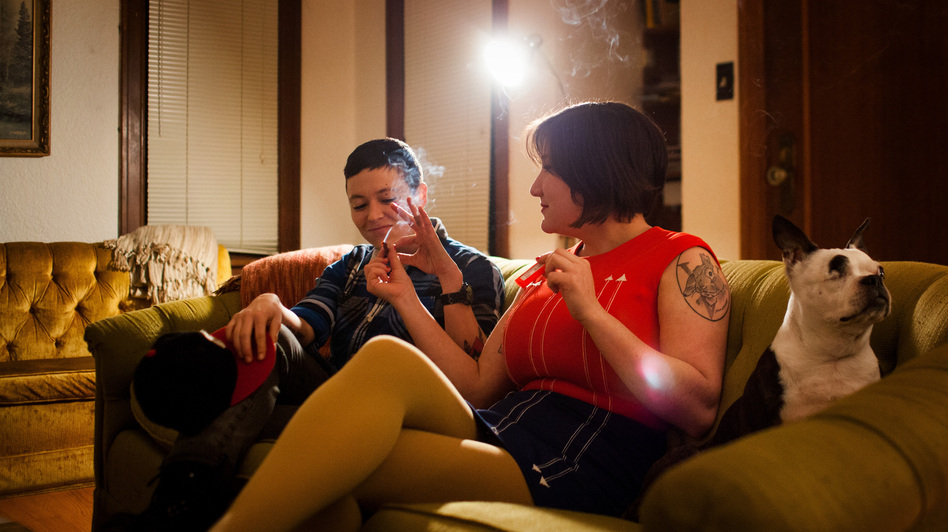 Cohen passes a joint to her friend Mika Loudon at her home in Seattle, Wash. (Jonathan Steinberg for NPR)
