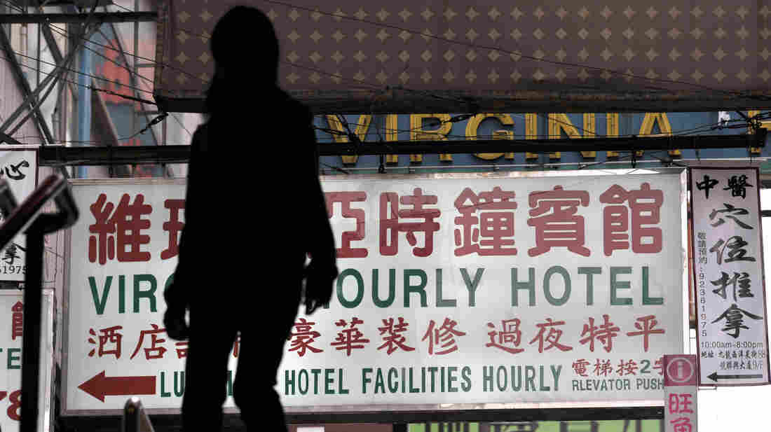"A passerby walks past a sign for an ""hourly hotel"" in a popular shopping district in Hong Kong. A recent anti-vice crackdown in China has targeted mistresses and sex workers."