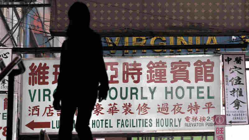 """A passerby walks past a sign for an """"hourly hotel"""" in a popular shopping district in Hong Kong. An recent anti-vice crackdown in China has targeted mistresses and sex workers as part of a social problem."""