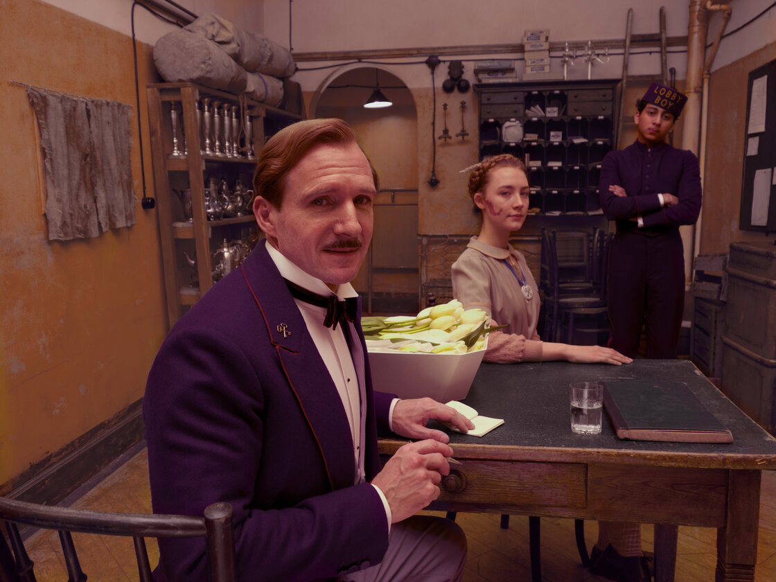 Ralph Fiennes portrays concierge Monsieur Gustave in The Grand Budapest Hotel, the actor' first project with director Wes Anderson.