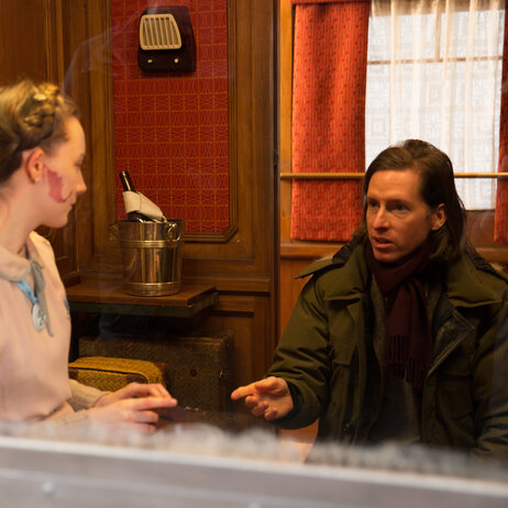 Wes Anderson at work, coaching his actors through their roles.