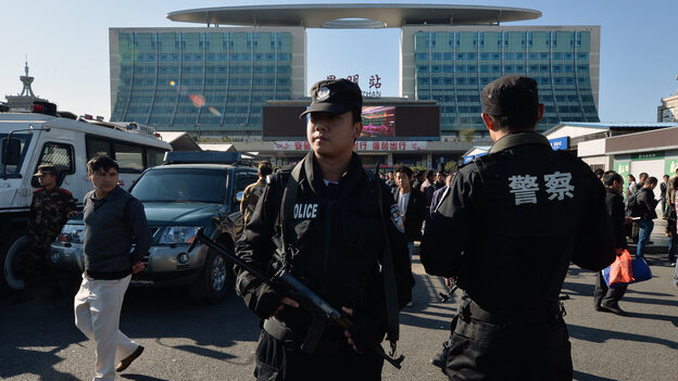 Chinese paramilitary police stand guard outside the scene of a terrorist attack at the main train station in Kunming, Yunnan Province, Monday. Knife-wielding assailants left at least 29 people dead in t