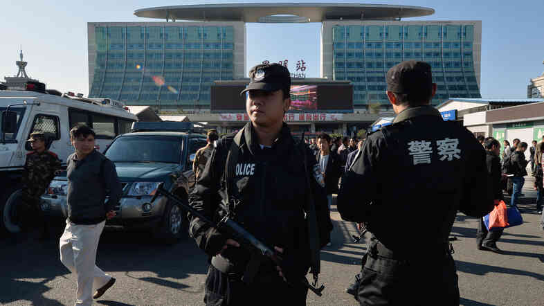 Chinese paramilitary police stand guard outside the scene of a terrorist attack at the main train station in Kunming, Yunnan Province, Monday. Knife-wielding assailants left at least 29 people dead in the attack.