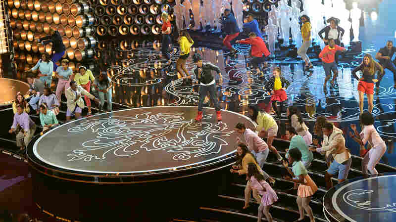 """Pharrell Williams, center, performs """"Happy"""" during the Oscars at the Dolby Theatre on Sunday, with the help of dancers who attend an L.A. high school (they're dressed in pastel colors)."""