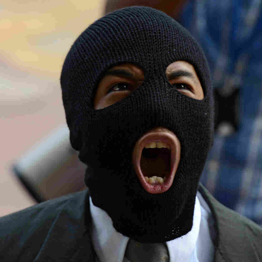 A balaclava-clad protester shouts anti-government slogans during a rally in Honduras.