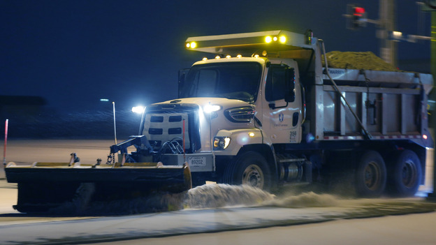 On the road again: This plow was at work on Sunday in Lawrence, Kan. The storm that hit there has spread east. (AP)