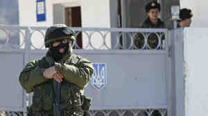 A soldier in an unmarked uniform, but believed to be from the Russian army, stands outside one of the Ukrainian military bases in Crimea that have been surrounded by Russian forces. Ukrainian guards look on from inside the base.