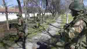 Armed men in military uniform, believed to be Russian soldiers, were outside the territory of a Ukrainian military unit in Bakhchisaray, on the Crimean Peninsula, on Monday.