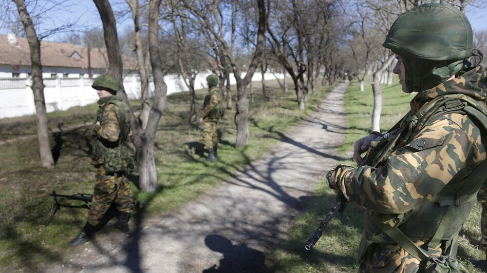 Armed men in military uniform, believed to be Russian soldiers, were outside the territory of a Ukrainian military unit in Bakhchisaray, on the Crimean Peninsula, on Monday. (EPA/LANDOV)