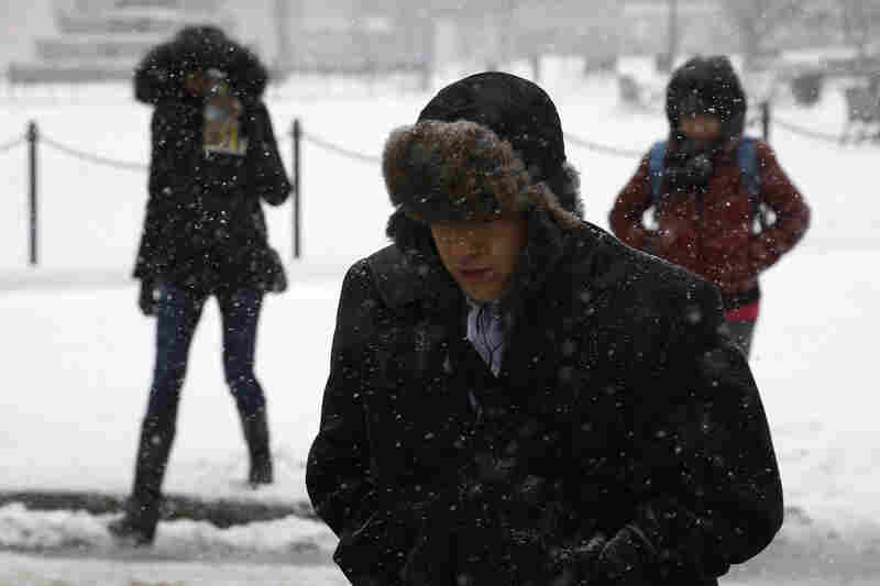 Pedestrians make their way through morning snow in downtown Washington, D.C., where federal offices are closed Monday. Schools canceled classes in many of the affected towns and cities.