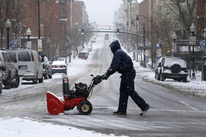 A man pushes a snow blower across a street as snow falls in Baltimore.