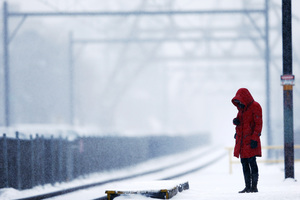 A commuter waits for a train as snow falls in Philadelphia.