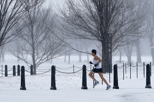 A runner braves the elements on the National Mall as snow falls in Washington, D.C.  Flight cancellations and delays started to build early Monday. FlightAware.com reported at least 2,000 flights had been canceled.