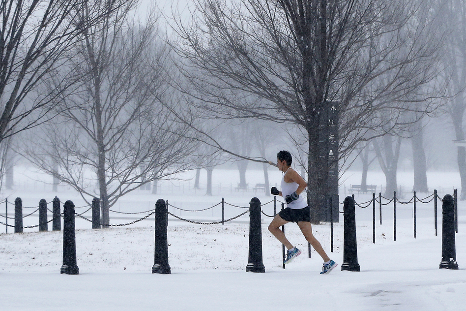 A runner braves the elements on the National Mall as snow falls in Washington, D.C.  Flight cancellations and delays started to build early Monday. FlightAware.com reported at least 2,000 flights had been canceled. (AP)