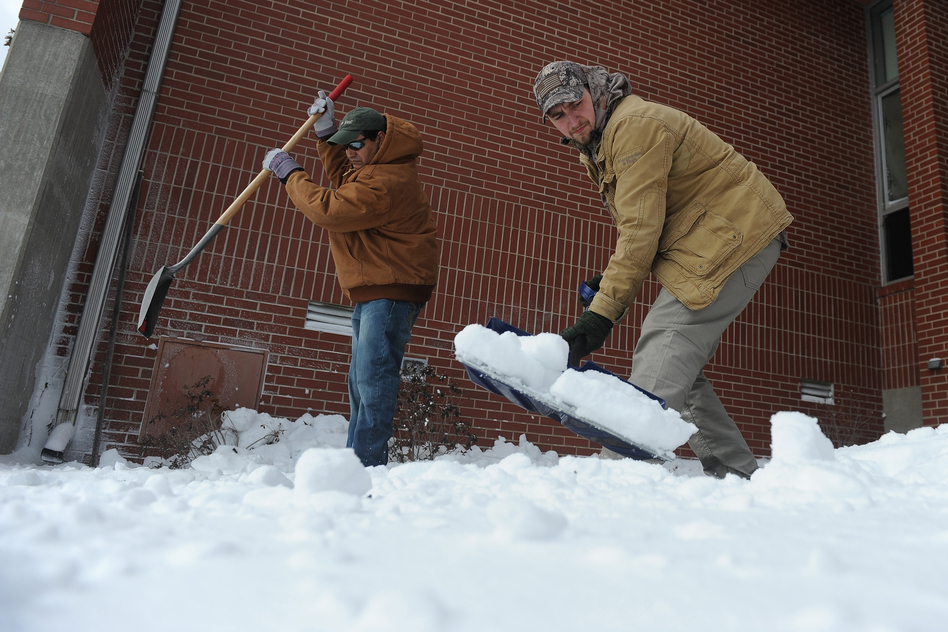 "Roberto Molina (left), and Austin Moore work to shovel snow in front of Clark Elementary in Paducah, Ky., on Monday. ""State highways officials say road crews are out this morning clearing roads, but warned that they are having a hard time keeping up with heavy snow, and told drivers to stay off the roads if possible,"" the Charleston Gazette in West Virginia reports. (AP)"