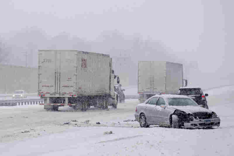 A car involved in a crash while traveling on Maryland Route 50 is passed by trucks during a snow storm in Bowie, Md.