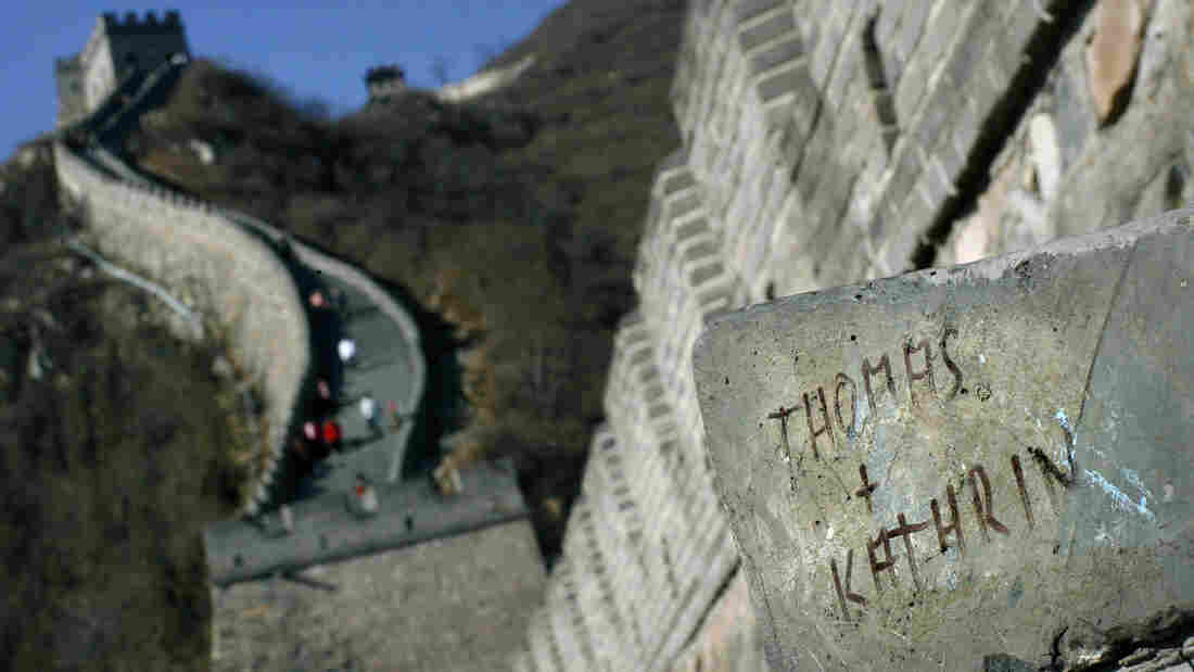 Two of the names carved into the Great Wall, in this case near Badaling, China. Authorities hope to cut down on graffiti by giving tourists a designated spot to leave their marks.