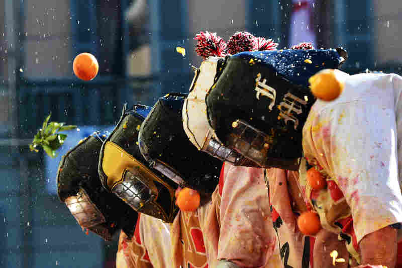 "Men with helmets are hit by oranges during the traditional ""battle of the oranges,"" held during the carnival in Ivrea, Italy. During the event, which marks the people's rebellion against tyrannical lords who ruled the town in the Middle Ages, revelers parading on floats represent guards of the tyrant, while those on foot are the townsfolk."