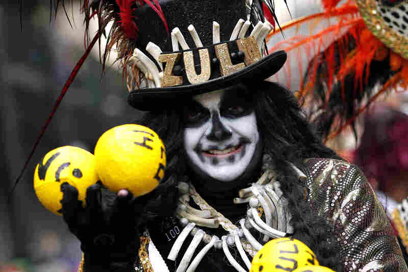 A member of the Krewe of Zulu parades down St. Charles Avenue on Mardi Gras Day in New Orleans.