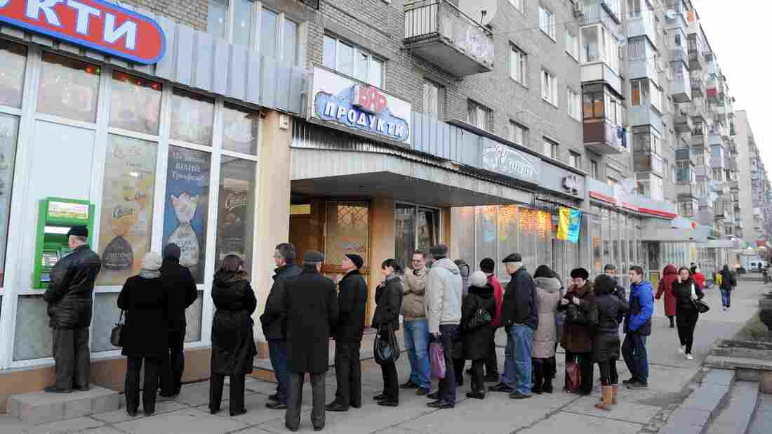 Ukrainians line up to get money from a bank machine in the western city of Lviv on Feb. 20. The country's political crisis has also created economic turmoil. The international community is expected to pump billions of dollars into Ukraine's struggling economy.