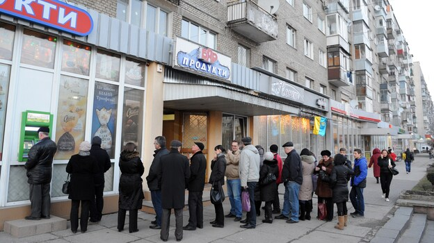 Ukrainians line up to get money from a bank machine in the western city of Lviv on Feb. 20. The country's political crisis has also created economic turmoil. The international community is expected to pump billions of dollars into Ukraine's struggling economy. (AFP/Getty Images)