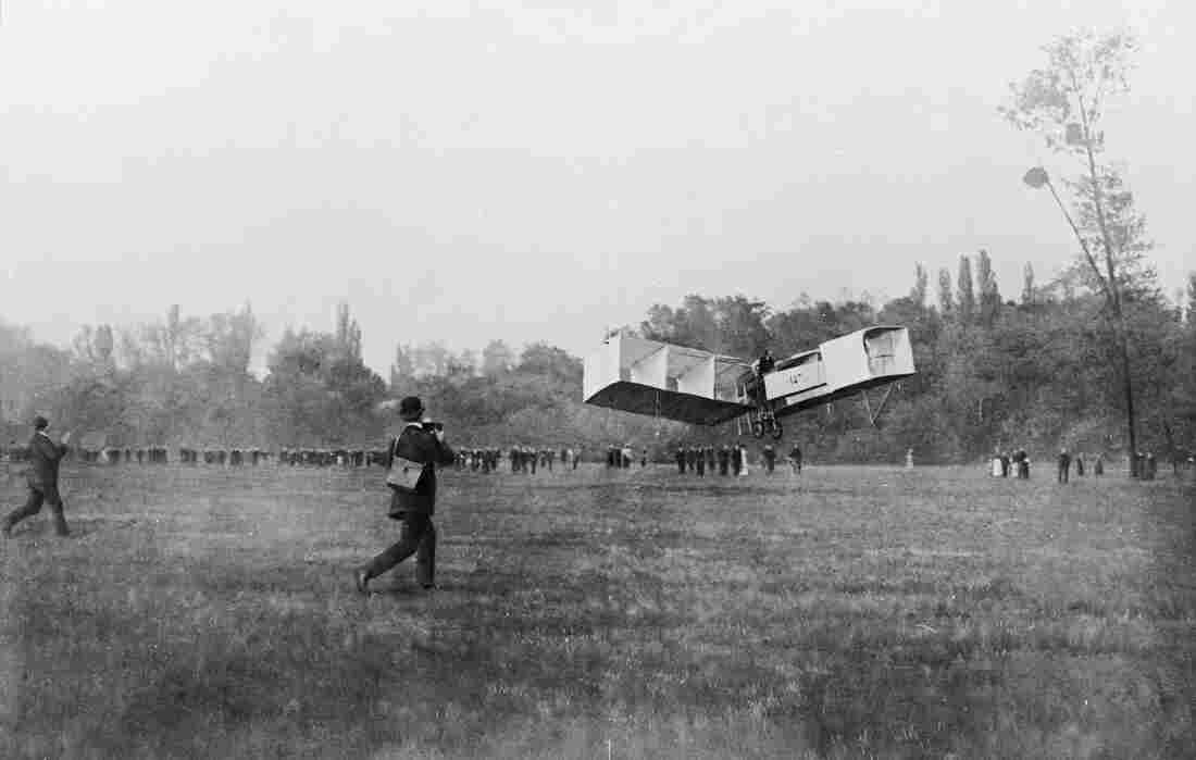Brazilian aviator Alberto Santos-Dumont's 14-bis biplane takes off from a French field in 1906.