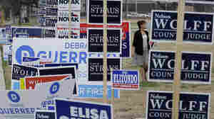 Rebecca Gonzalez searches for a location for an election sign at an early voting polling site Feb. 18 in San Antonio, Texas.
