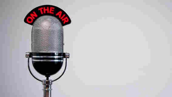 Retro microphone with an 'On the Air' illuminated sign on a desk.