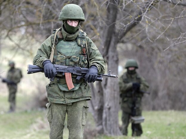 "Armed men in unmarked military uniforms — who witnesses believe are Russian troops, but who Russian leaders say are ""local self-defense"" forces — stand outside the territory of a Ukrainian military unit in the Crimean village of Perevalnoye."