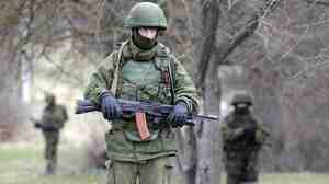 """Armed men in unmarked military uniforms — who witnesses believe are Russian troops, but who Russian leaders say are """"local self-defense"""" forces — stand outside the territory of a Ukrainian military unit in the Crimean village of Perevalnoye."""