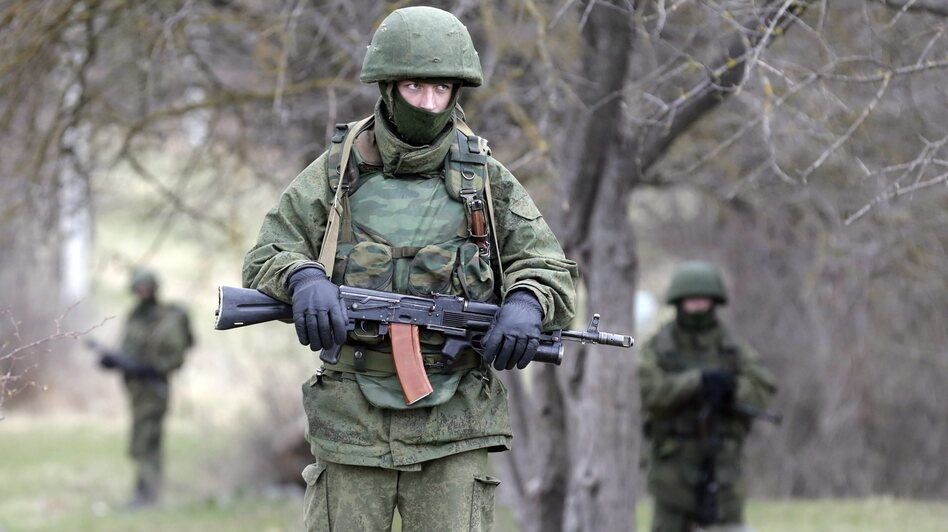 "Armed men in unmarked military uniforms — who witnesses believe are Russian troops, but who Russian leaders say are ""local self-defense"" forces — stand outside the territory of a Ukrainian military unit in the Crimean village of Perevalnoye. (EPA/Landov)"