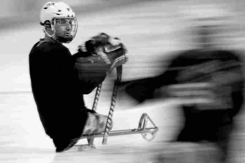 Players strap on to a tiny sled perched a few inches off the ice and balance on one double-runner skate. They use two short sticks as poles to fly across the ice.