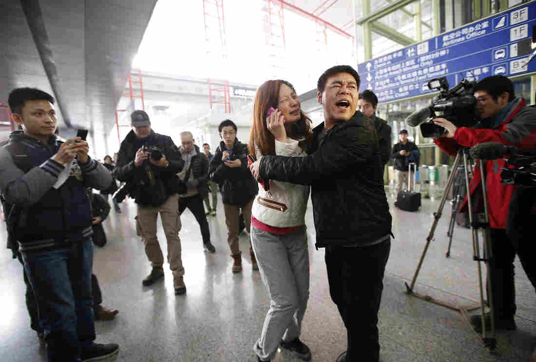 A woman, believed to be the relative of a passenger onboard Malaysia Airlines flight MH370, cries as she talks on her mobile phone at the Beijing Capital International Airport in Beijing.