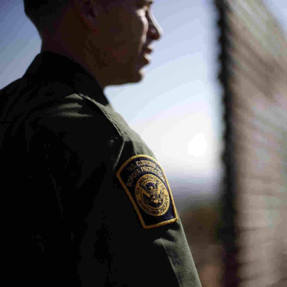 A Border Patrol agent looks to the north near where the border wall ends as it separates Tijuana, Mexico, left, and San Diego.