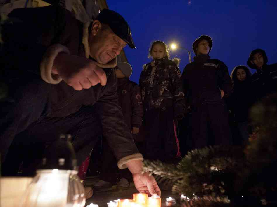 People light candles during a commemoration to pay tribute to victims of a series of deadly attacks against Roma or Gipsy people in Budapest, Hungary, Feb. 23, 2012.