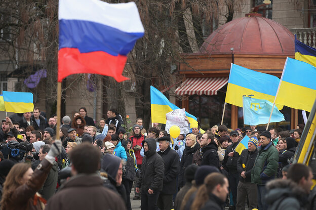 Pro-Russian marchers (foreground) walk past pro-Ukrainian marchers gathered in Simferopol, capital of Ukraine's Crimea region, Saturday. Several hundred pro-Ukrainian protesters marched peacefully through the city center to a Ukrainian military base that's been blockaded by pro-Russian militants and soldiers.