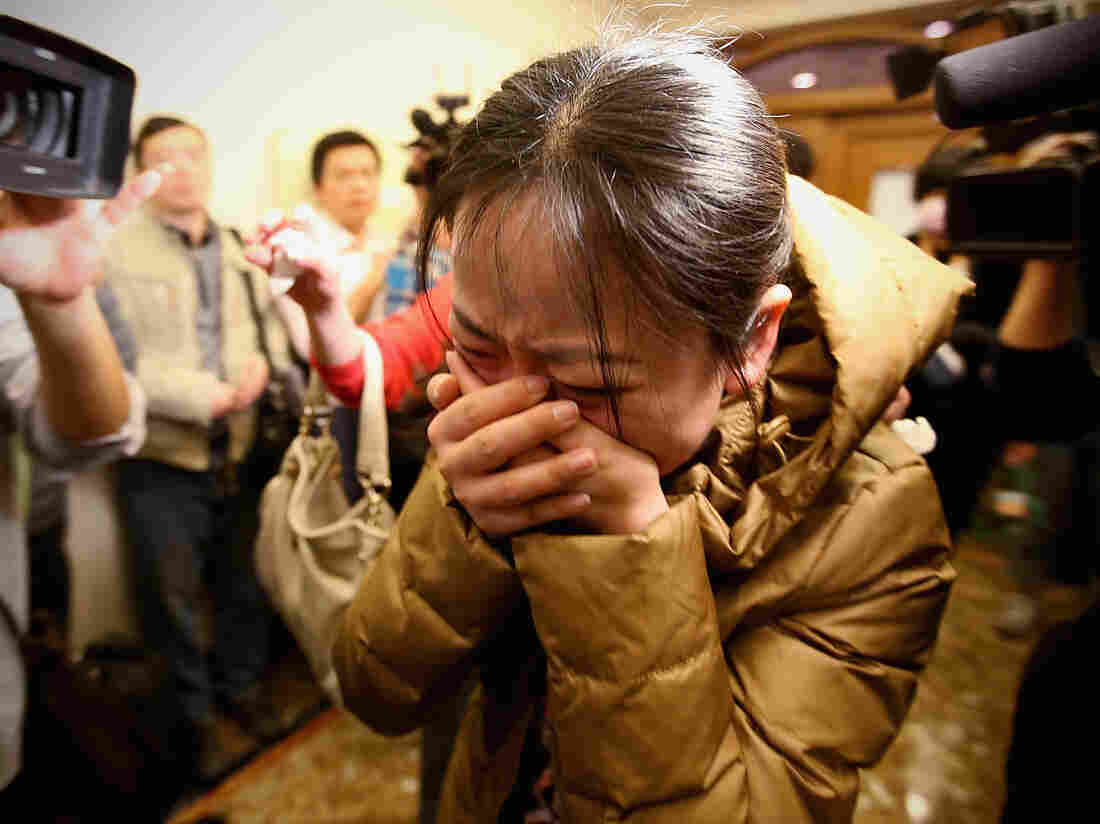 A relative of a passenger onboard Malaysia Airlines flight MH370 cries at a Beijing hotel where family members were gathered.
