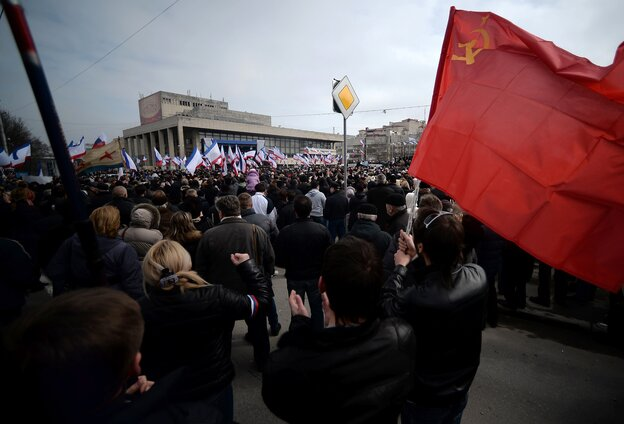 """A man holds a Soviet Union flag during a pro-Russia rally in Simferopol, Crimea's Lenin Square Sunday. In Kiev, Ukrainian Prime Minister Arseniy Yatsenyuk vows not to give """"an inch"""" of territory to Russia."""