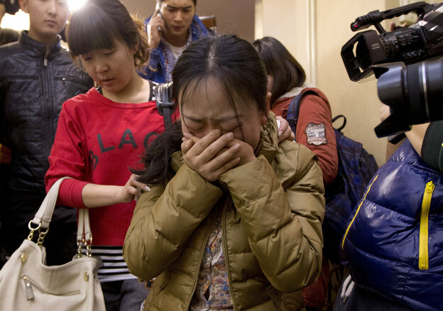 A relative of passengers aboard a missing Malaysia Airlines flight is escorted from a Beijing hotel room for loved ones of the passengers on Sunday.