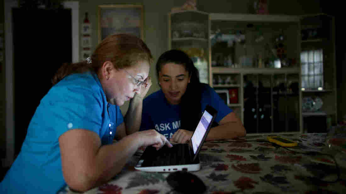 Janelle Arevalo, an insurance agent with Sunshine Life and Health Advisors, makes a house call in Miami to sign up Sandra Berrios (left) for an insurance plan under the Affordable Care Act.