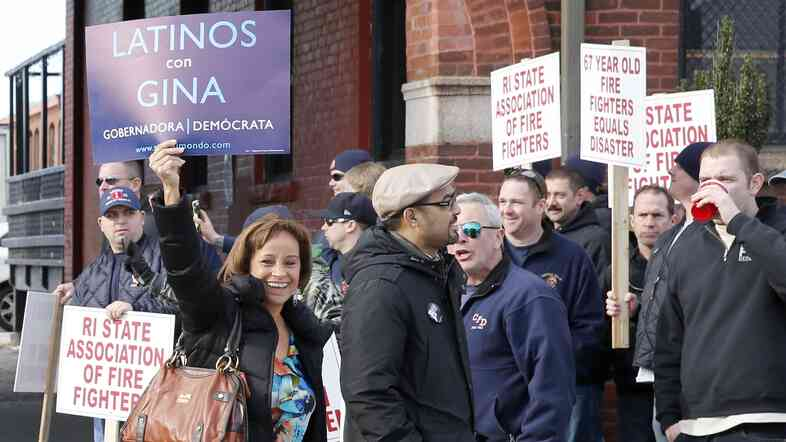 Two supporters of gubernatorial candidate Gina Raimondo walk past protesting union members outside a rally at which Raimondo announced her run for the