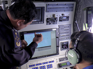 Adm. Mohd Amdan Kurish of the Malaysian Maritime Enforcement Agency Admiral, left, checks radar during a search for the missing Malaysia Airlines plane off Tok Bali Beach in Kelantan, Malaysia, on Sunday.